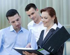 female boss showing her employees something in a folder - stock photo