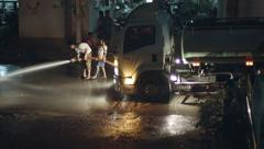 Phuket, kamala, thailand - circa aug 2014: locals wash asphalt on the highway Stock Footage
