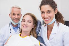 Dentist his assistant and patient all smiling at camera Stock Photos