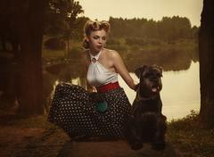 retro style. the girl with a dog in a park in sunset rays. - stock photo