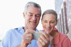 Happy senior couple looking at smartphone - stock photo