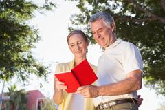 Happy senior couple using the guidebook - stock photo