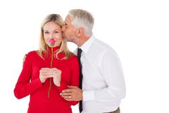 Stock Photo of Handsome man giving his wife a kiss on cheek