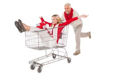 Festive couple messing about in shopping trolley - stock photo