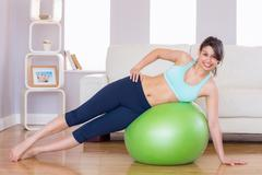 Stock Photo of Fit brunette in plank position on exercise ball