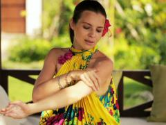 Beautiful woman applying moisturizing cream on her arm in garden NT Stock Footage