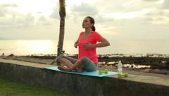 Woman doing breathing exercise by the sea in the evening HD Stock Footage