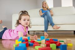 Stock Photo of Girl playing with building blocks while mother on conch