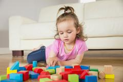 Stock Photo of Girl playing with building blocks on floor