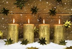 Stock Illustration of four golden burning candles for advent on wooden rustic background.