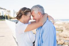 Happy casual couple hugging by the coast - stock photo