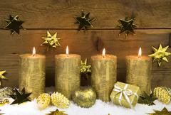 Four golden burning christmas candles for advent decoration. Kuvituskuvat
