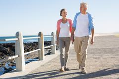 Stock Photo of Happy casual couple walking by the coast