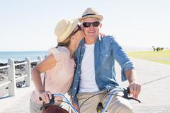 Stock Photo of Happy casual couple going for a bike ride on the pier