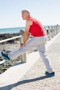 Stock Photo of Fit mature man warming up on the pier