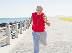 Fit mature man jogging on the pier - stock photo