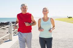 Fit mature couple jogging on the pier - stock photo