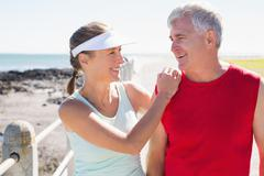 Fit mature couple warming up together on the pier - stock photo