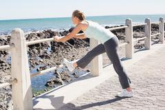 Fit mature woman warming up on the pier - stock photo
