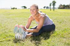Stock Photo of Fit mature woman warming up on the grass
