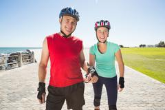 Fit mature couple rollerblading on the pier - stock photo
