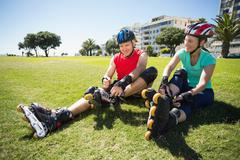 Stock Photo of Fit mature couple tying up their roller blades on the grass