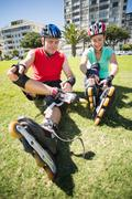 Fit mature couple tying up their roller blades on the grass - stock photo