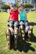 Fit mature couple wearing roller blades on the grass - stock photo