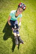 Fit mature woman in roller blades on the grass - stock photo