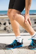 Fit man gripping his injured calf muscle - stock photo