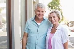 Stock Photo of Happy mature couple smiling at camera in the city