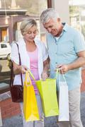 Happy mature couple looking at their shopping purchases - stock photo