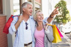 Stock Photo of Happy mature couple walking with their shopping purchases