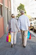Happy mature couple walking with their shopping purchases - stock photo