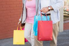 Happy mature couple walking with their shopping purchases Stock Photos