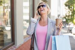 Stock Photo of Happy mature woman walking with her shopping purchases