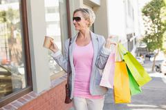 Happy mature woman walking with her shopping purchases - stock photo