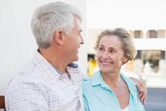 Happy mature couple sitting on bench in the city - stock photo