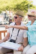 Stock Photo of Happy tourist couple looking at map in the city