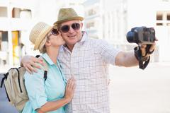 Happy tourist couple taking a selfie in the city Stock Photos
