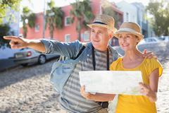 Stock Photo of Happy tourist couple using map in the city