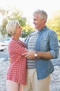 Stock Photo of Happy mature couple hugging in the city