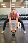 Full length of woman lifting kettle bell in gym Stock Photos