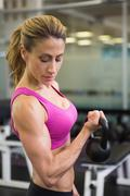 Fit woman lifting kettle bell in gym Stock Photos