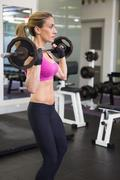 Fit young woman lifting barbell in the gym - stock photo