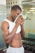 Fit man wiping sweat after workout in gym - stock photo
