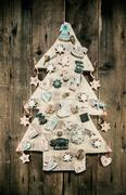 Christmas decoration: wooden carved tree decorated with gingerbread. Stock Photos