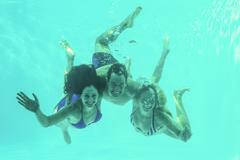 Friends underwater in swimming pool - stock photo