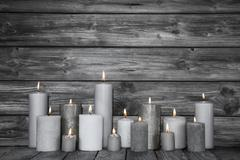 Burning candles in white and grey on wooden shabby chic background. Stock Photos