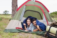 Stock Photo of Happy couple lying in tent on countryside landscape